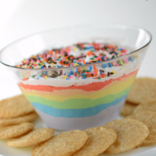 rainbow dip with cookies around on cake plate with words