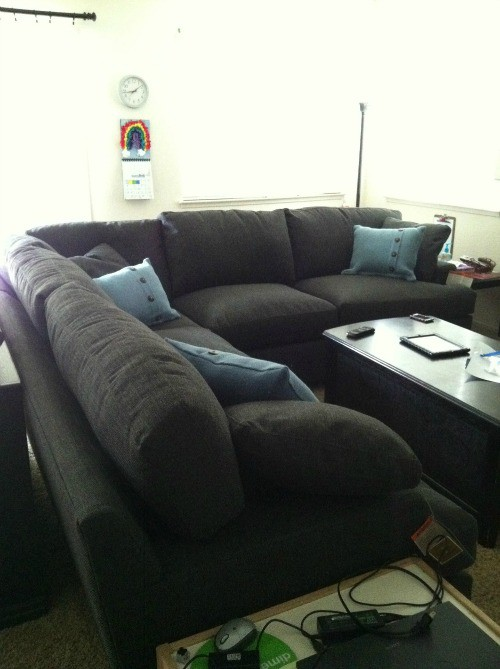 Photo of the new sectional couch that is dark grey with blue pillows