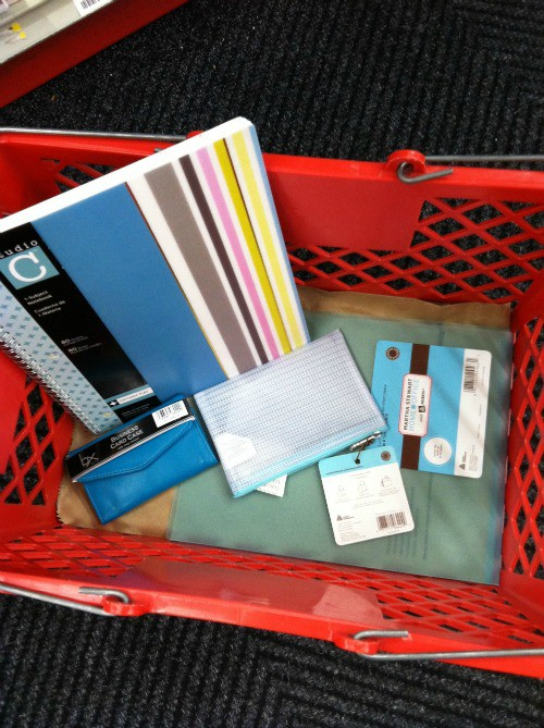 Red shopping basket filled with office supplies like notebooks and pencil case
