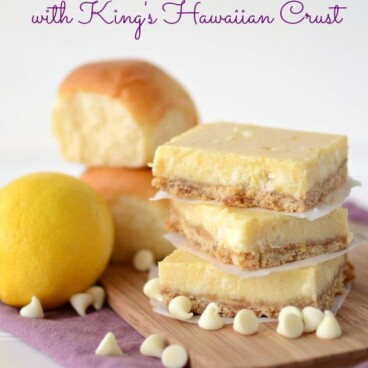 lemon bars in a stack on cutting board with rolls behind and lemon and words on photo
