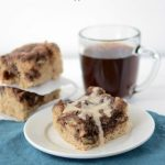 Mocha Coffee Cake piece on a white plate with blue napkin and more coffee cake and coffee in the background