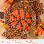 Overhead shot of Reese's basketball dip with candy and pretzels around it and text on bottom of the photo