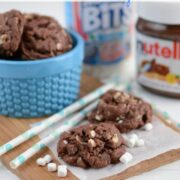 Rocky road cookies on a wood cutting board with straws and ingredients in the background