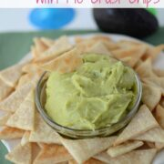 Sweet Guacamole Dip in a glass bowl with Pie Crust Tortilla Chips around it on a serving plate with recipe title on top of image