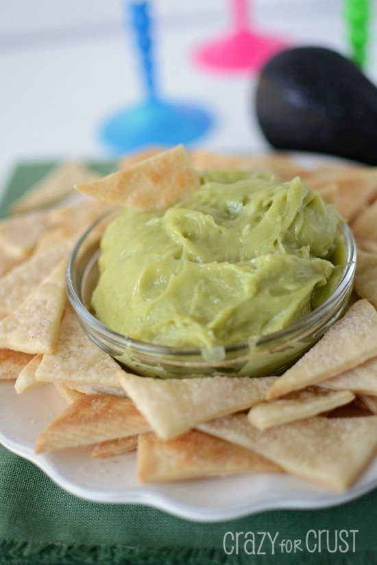Sweet Guacamole Dip in a glass bowl with Pie Crust Tortilla Chips around it on a serving plate