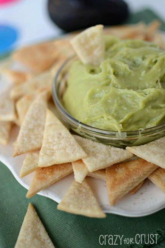Closeup photo of Sweet Guacamole Dip in a glass bowl with Pie Crust Tortilla Chips around it on a white serving plate