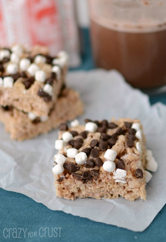 Hot Chocolate Krispie Treats with marshmallows and chocolate chips on parchment paper with hot cocoa in back