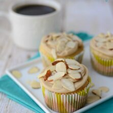 almond cupcakes with caramel frosting and almonds on top on white plate with teal napkin and coffee behind