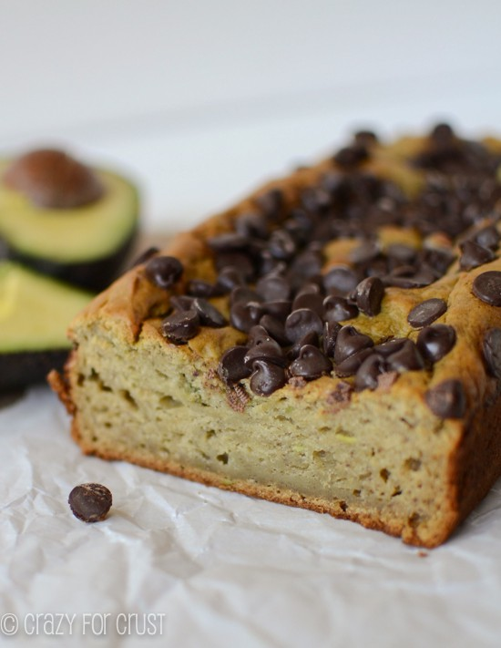 avocado banana bread sliced on parchment paper with avocado behind