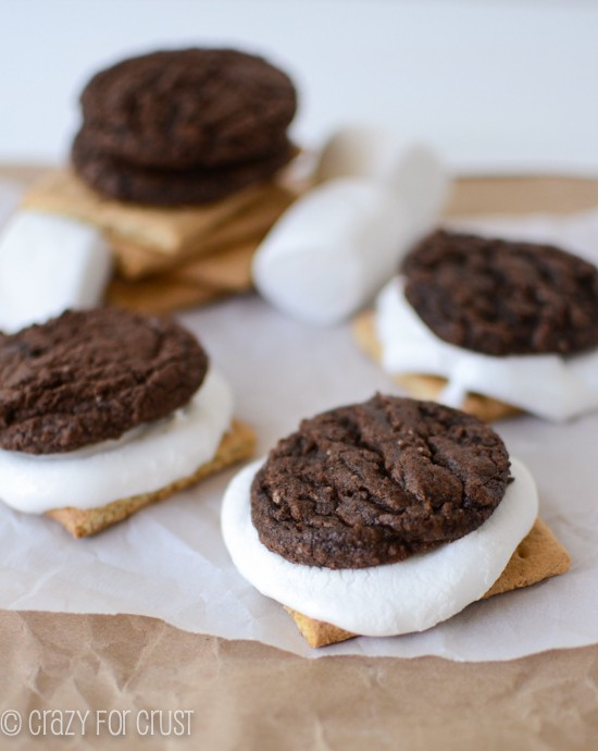 brownie cookie sandwiched with melted marshmallow and graham cracker on parchment paper