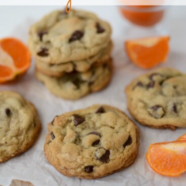 chocolate chip cookies on parchment with oranges around the cutting board