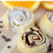 orange sweet rolls with and without icing on cutting board with words on photo