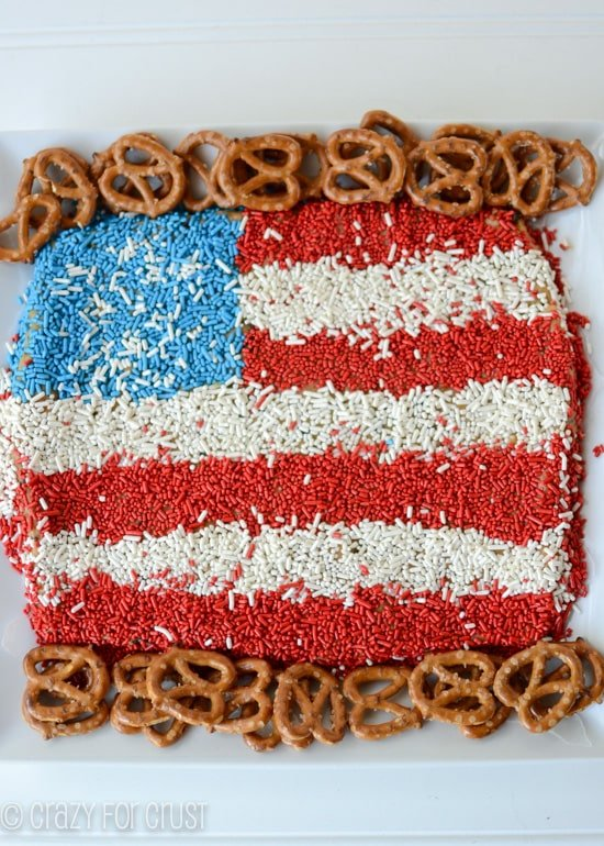 peanut butter dip made to look like a flag with red white and blue sprinkles and pretzels around it on white background
