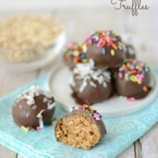 peanut butter oatmeal truffles coated in chocolate on white plate and teal napkin with one truffle cut in half and words on photo
