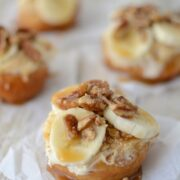 fried doughnut on parchment paper topped with bananas nuts and caramel