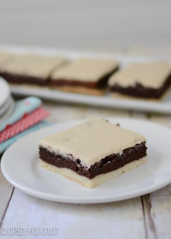 brownies with a crust and mocha frosting on white plate