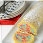 cake roll with blue and red filling on white plate