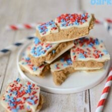 Stack of patriotic peanut butter cookie dough bars with red and blue sprinkles on a white plate on white wood table with words on top of photo
