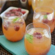 raspberry arnold palmer drink in stemless wine glasses on teal napkin