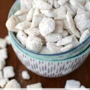 cinnamon roll muddy buddies coated in powdered sugar in two bowls on brown table