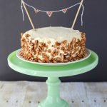 carrot cake ice cream cake with nuts outside on green cake stand