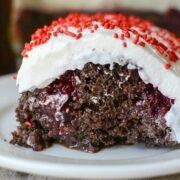 slice of cherry coke poke cake on white plate