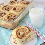 peanut butter cinnamon roll on white plate with teal napkin and pan of rolls behind
