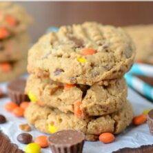 stack of peanut butter cookies with Reese's candy around it on brown table