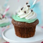 chocolate cupcake with green frosting and whipped cream with straw sitting on mini cake plate
