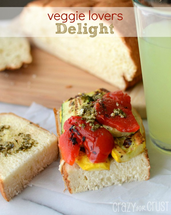 Open faced Veggie Lovers Delight sandwich on parchment paper with loaf of bread and lemonade in background