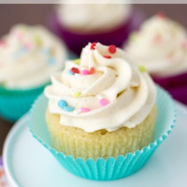 vanilla cupcake with frosting and sprinkles in teal wrapper on white mini cake stand