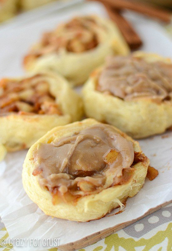 caramel apple cinnamon rolls with caramel frosting on parchment
