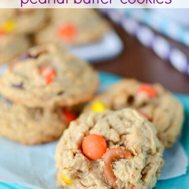 peanut butter cookies with candy and pretzels on parchment and teal napkin