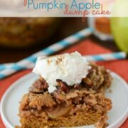 pumpkin apple dump cake slice on white plate with whipped cream