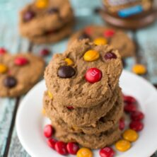 stack of dark chocolate peanut butter cookies on white plate with red and gold m and ms