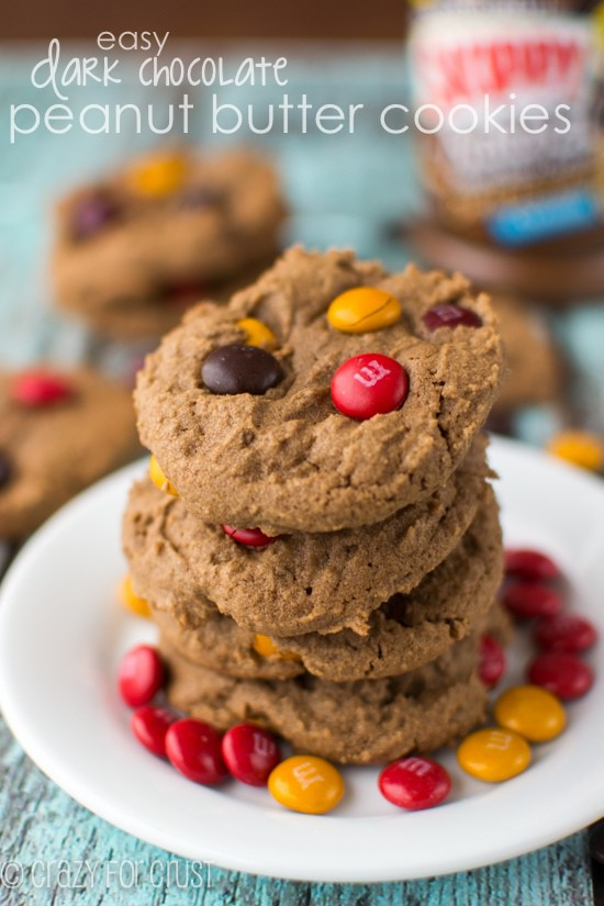 Stack of Easy Dark Chocolate Peanut Butter Cookies on a white plate with m&ms and recipe title in text on top of photo