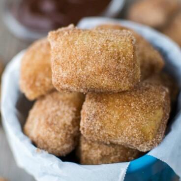 cinnamon sugar soft pretzel bites in blue dish with parchment paper and hot fudge behind