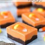 pieces of halloween fudge with chocolate bottom and orange top and candy corn on parchment and burlap