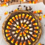 overhead shot of chocolate chip cookie cake topped with chocolate and candy corn patter with candy corn around it