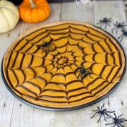 cookie pizza topped with orange frosting and spider web pattern in pizza pan on table