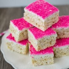 toasted coconut rice krispie treats on white plate with hot pink sugar on top
