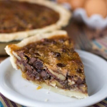 slice of pecan pie with chocolate chips and toffee on white plate with striped napkin