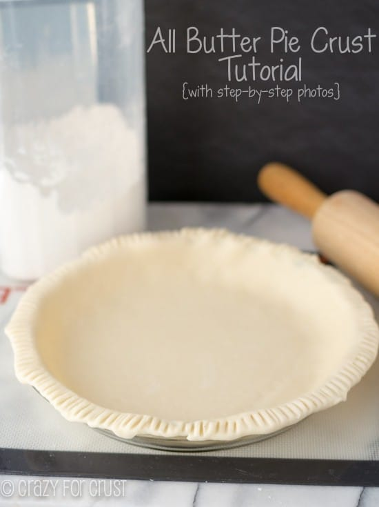 All Butter Pie Crust in pie dish with sides pinched and rolling pin and flour behind the crust