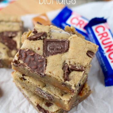 overhead shot of stack of blondies with crunch bars in them and crunch bars behind