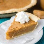 slice of peanut butter chess pie on white plate with teal napkin