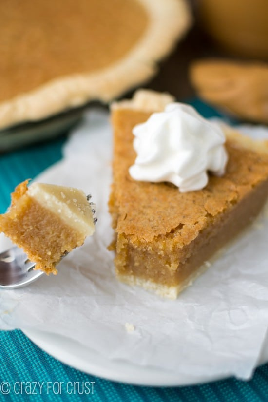 Close up shot of slice of Peanut Butter Chess Pie with one bite being taken out of with a fork