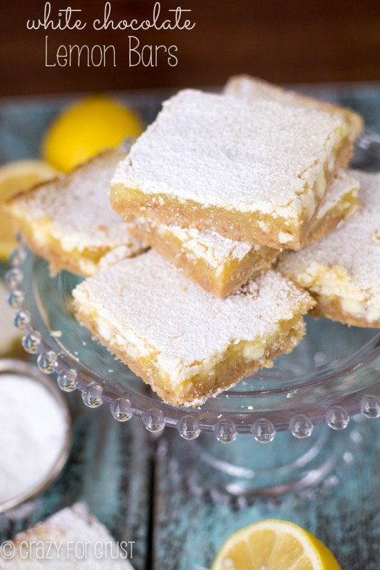 White Chocolate Lemon Bars on glass cake pedestal with title