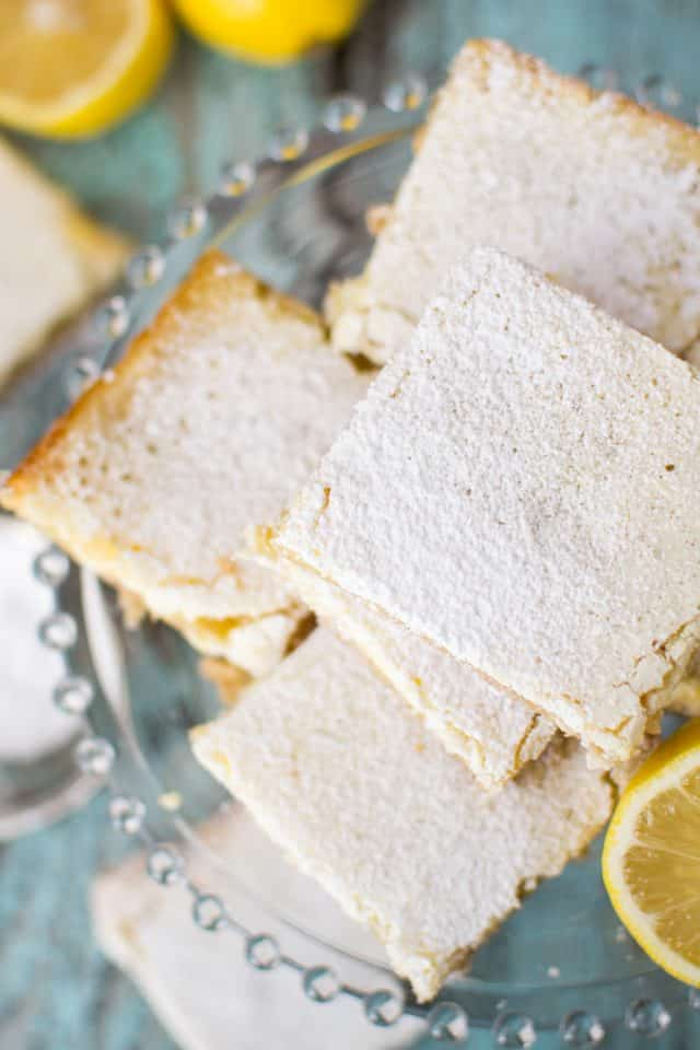 Overhead shot of white chocolate lemon bars on a clear plate.