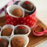 mexican chocolate truffles in white candy liners on cutting board