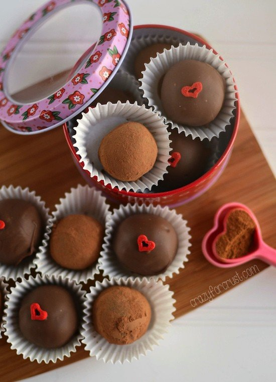 Overhead shot of mexican chocolate truffles on a wooden cutting board with heart decorations